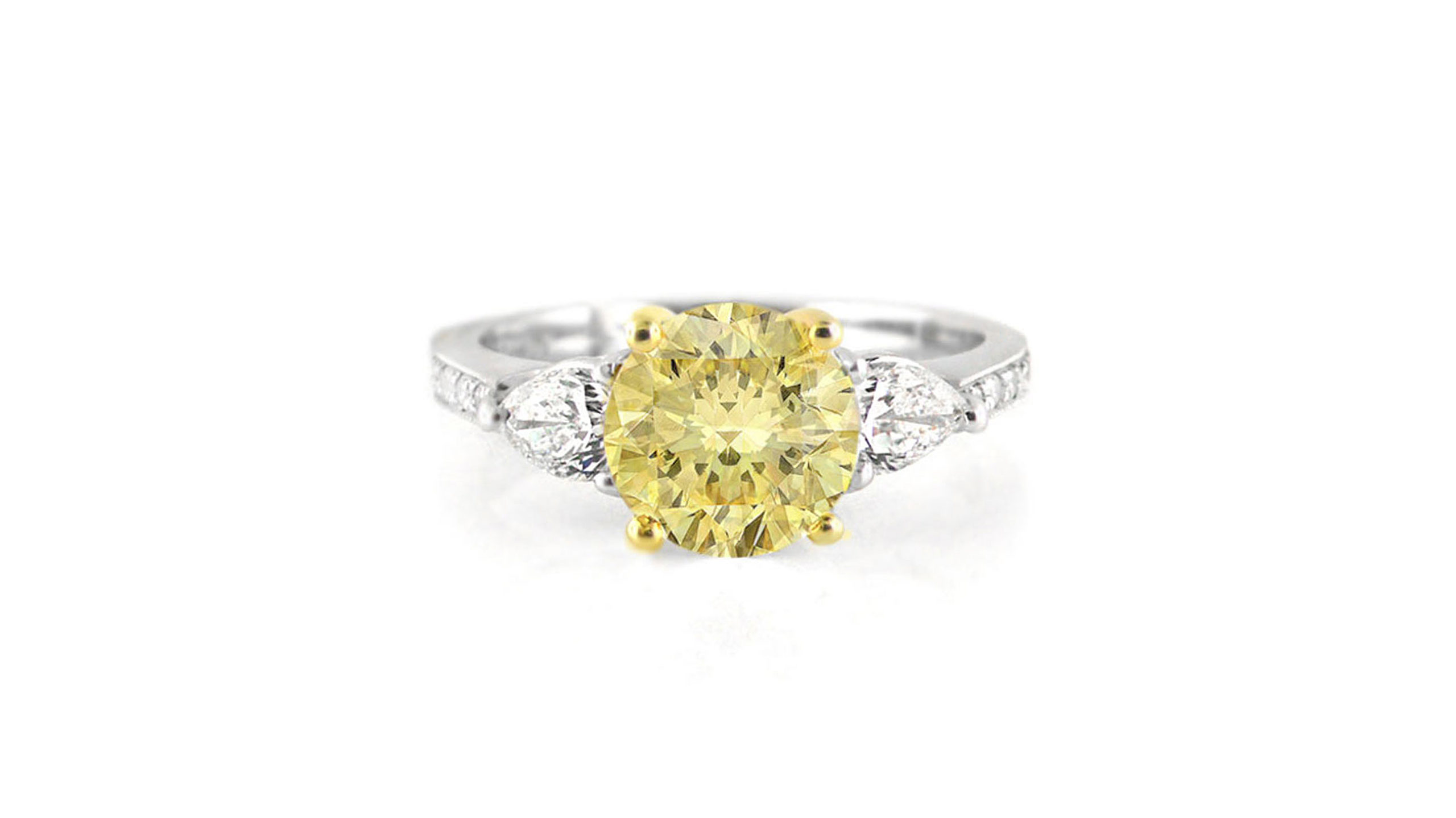 round & pear diamond trilogy ring set in platinum and yellow gold