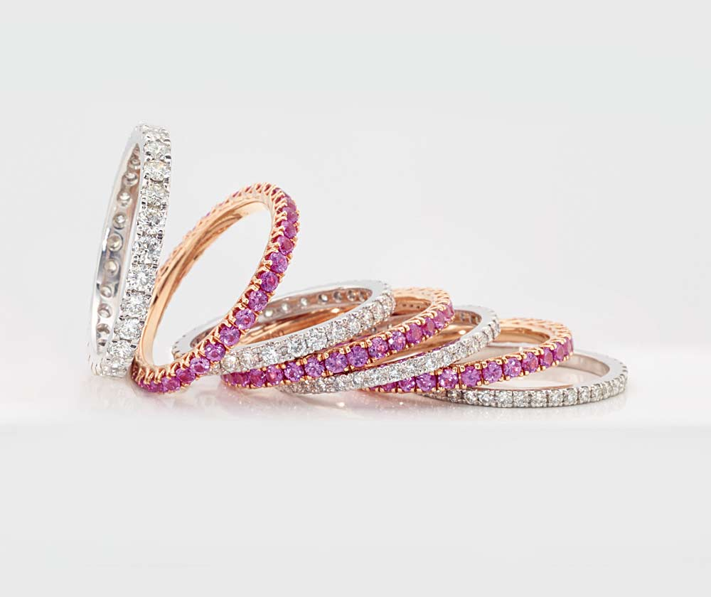 Pink sapphire coloured gemstone and diamond eternity bands