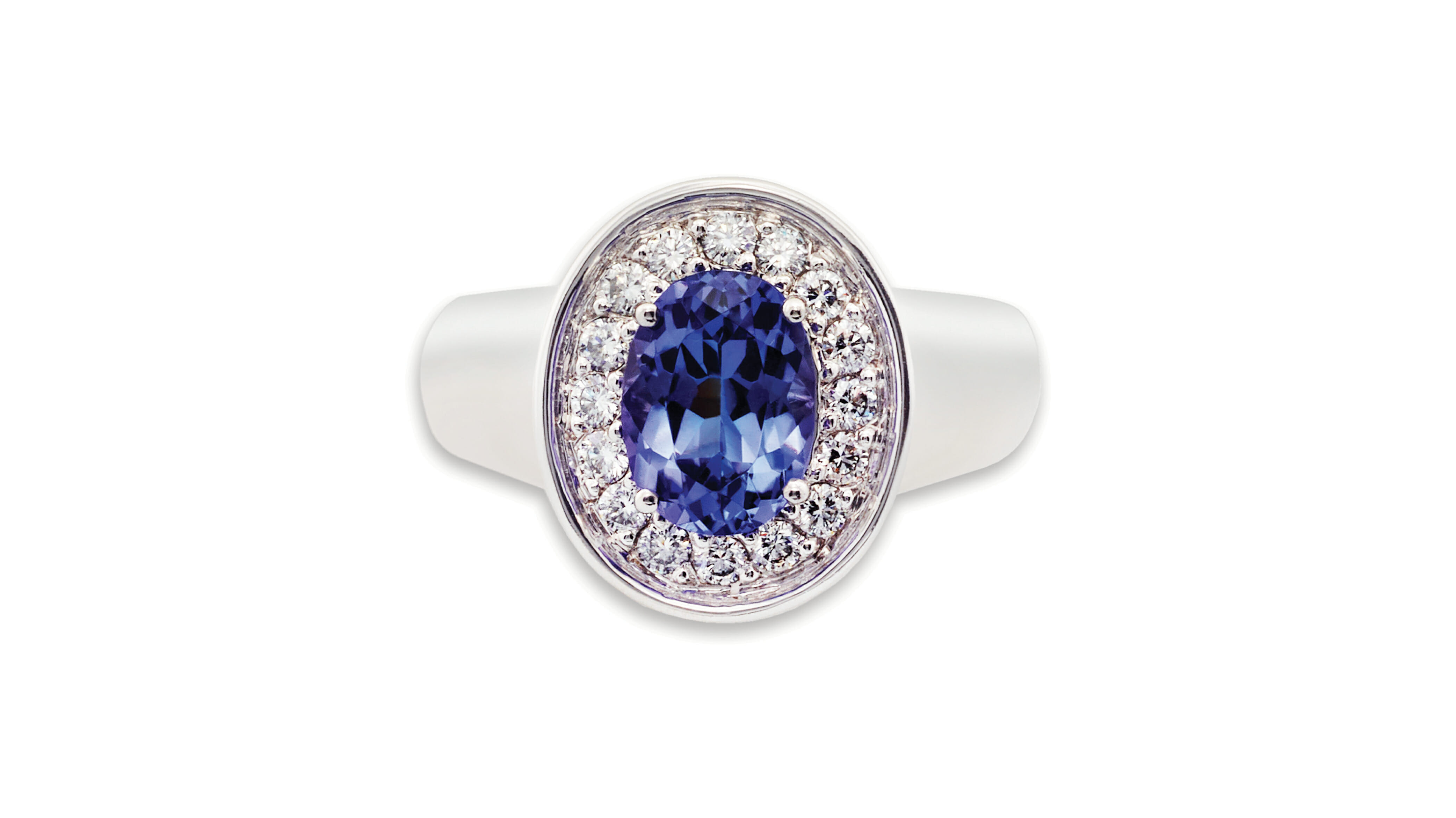 Tanzanite and diamond broad ring | A rare African tanzanite set in white gold, surrounded by a halo of sparkling diamonds