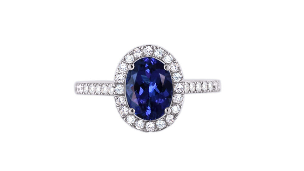 Oval Tanzanite and diamond ring | A small oval-shaped tanzanite, surrounded by a halo of diamonds, with a diamond encrusted band