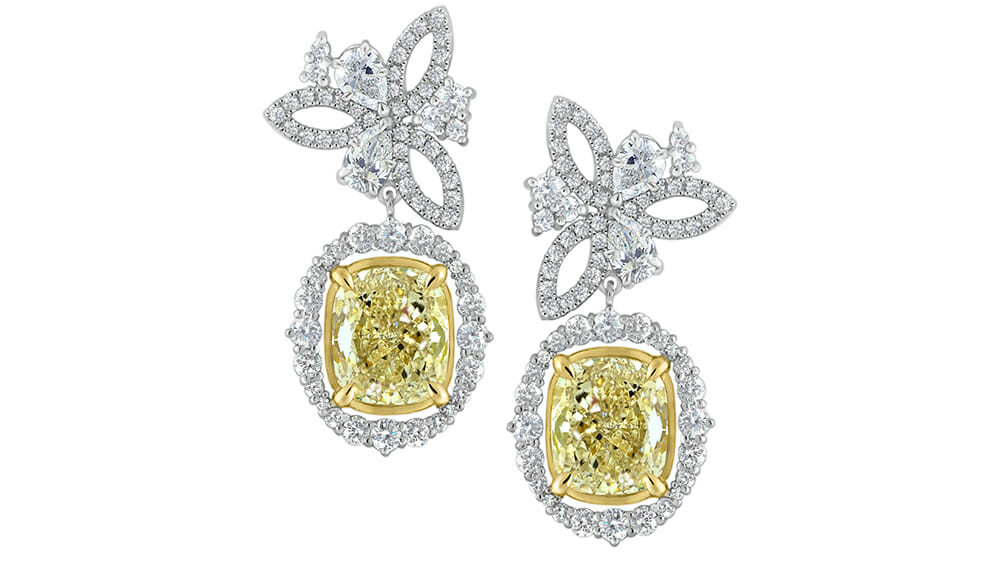A floral cluster of pear and round shaped diamon studs | A sparkling celestial design of yellow cushion cut diamonds surrounded by a halo of white diamonds suspended from floral studs