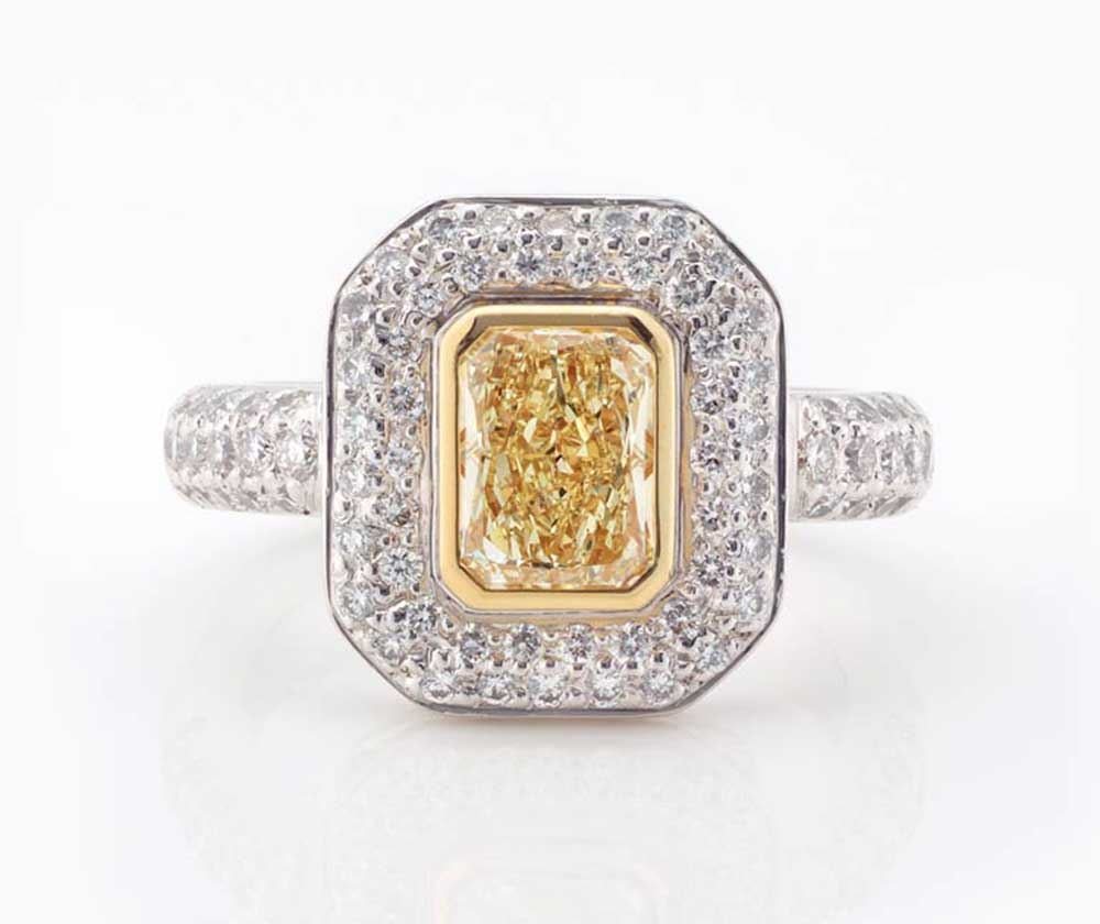 Diamond Dress Ring | A stunning yellow cushion cut diamond surrounded by a double halo of diamonds, with diamonds extending down the sides of the band