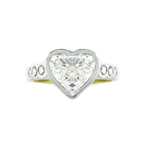 diamond heart ring | An 18 carat white and yellow gold vintage style diamond ring with a heart-shaped diamond and diamonds down the band