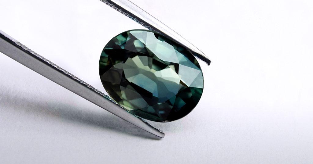 Stunning Peacock Sapphire in tweezers   Mark Solomon Jewellers